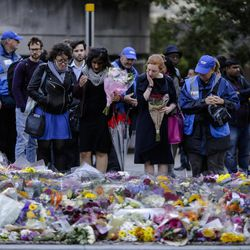 People look at floral tributes on London Bridge in London, Tuesday, June 6, 2017. British police on Tuesday named the third London Bridge attacker as an Italian national of Moroccan descent, and Italian officials said they had passed on their concerns about him to British intelligence officials last year.