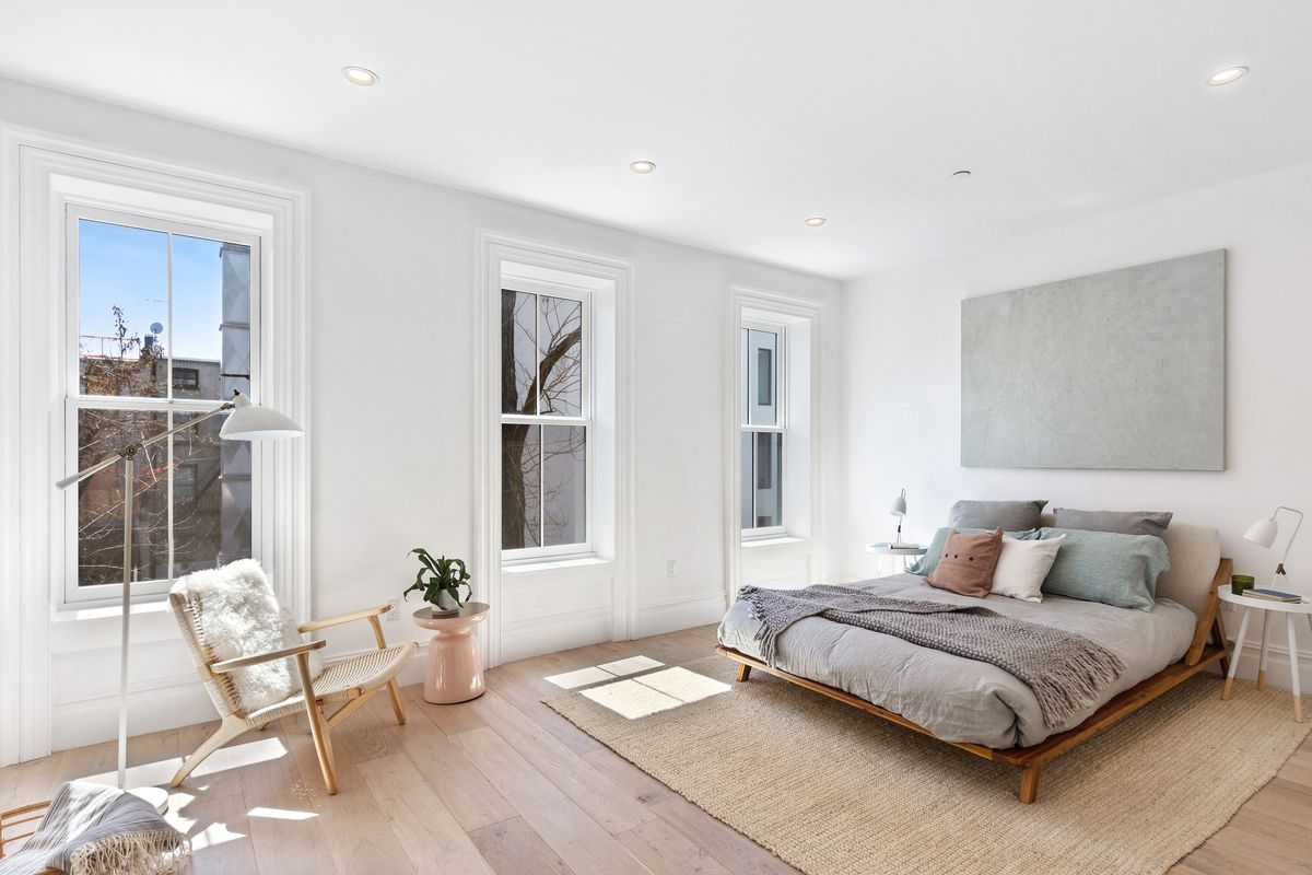 A bedroom with three large windows, hardwood floors, white walls, and a bed.