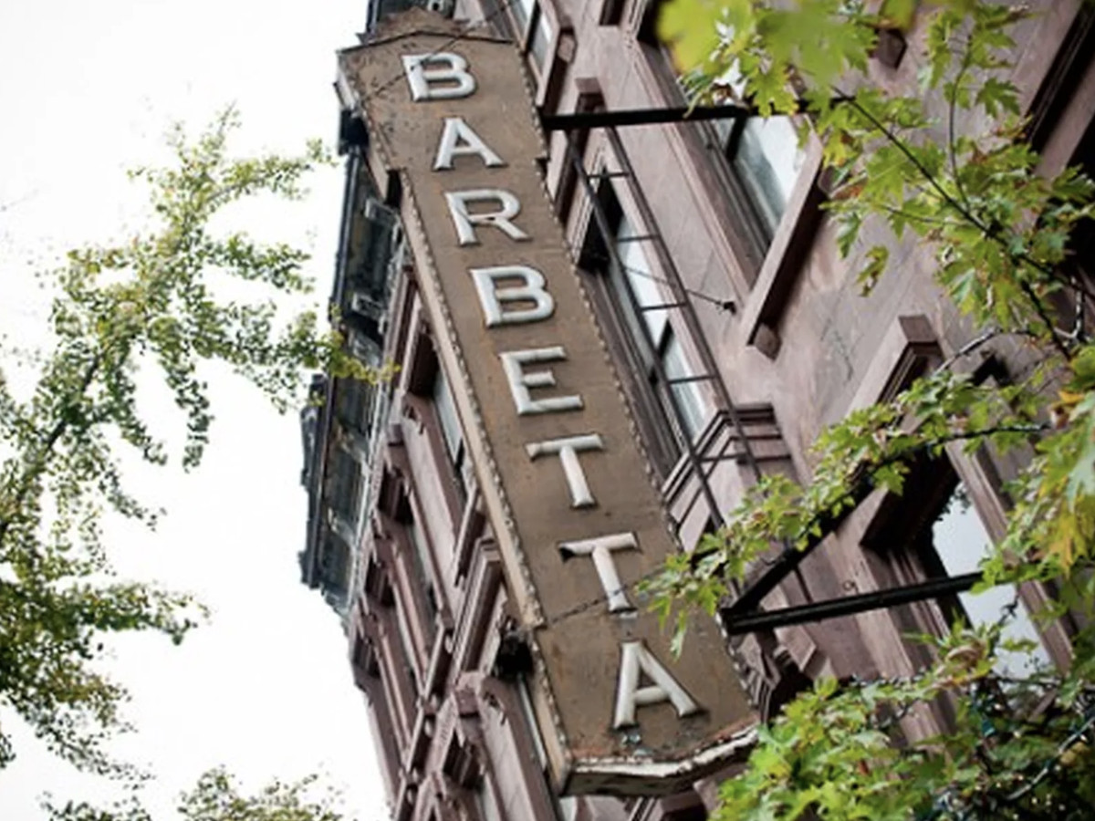 """A large, metal sign spans the length of a three-story building with the word """"Barbetta"""" in all capital letters"""