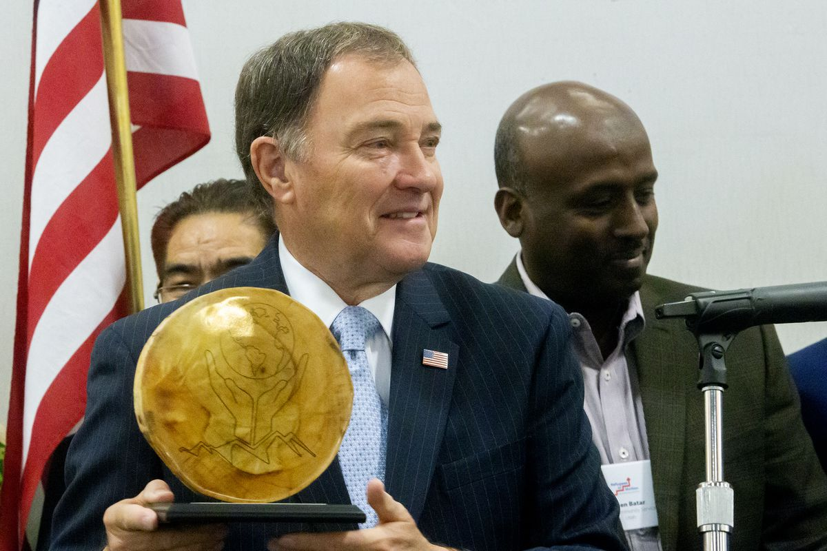Gov. Gary Herbert smiles as he holds a lifetime achievement award from Utah's refugee community during the Refugee Employment Conference at the Sheraton Salt Lake City Hotel on Friday, May 31, 2019.