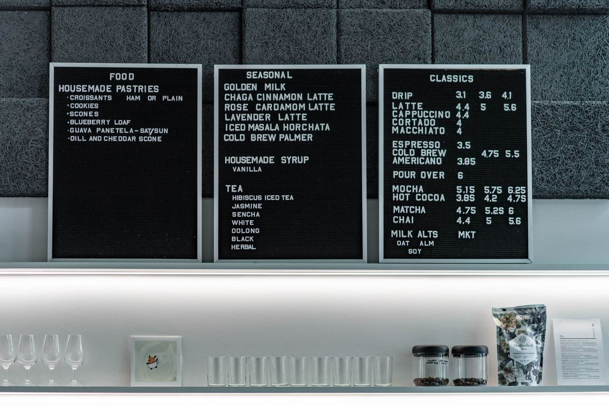 The black-slated menus at Union Coffee, with a list of food and beverage offerings and prices, lined up above the coffee bar