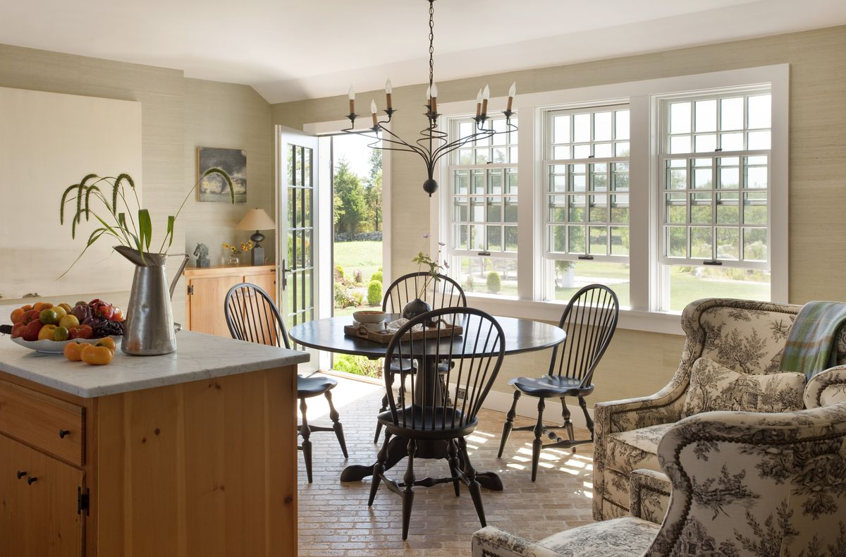 A kitchen area has a small black table with four chairs and windows out to the backyard.
