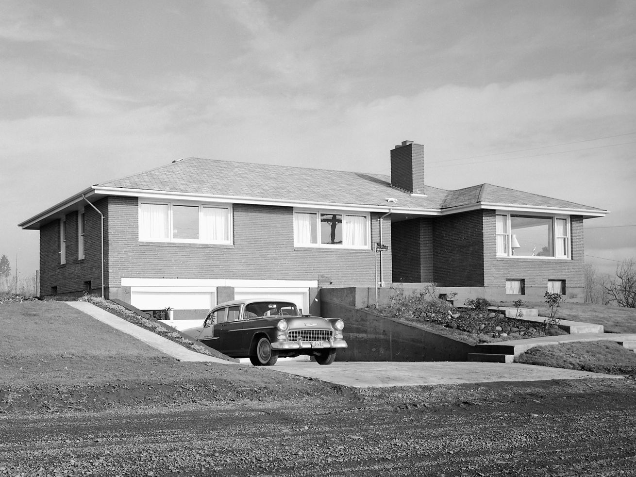 Chevrolet automobile in the driveway of a new home in Washington state in 1957.