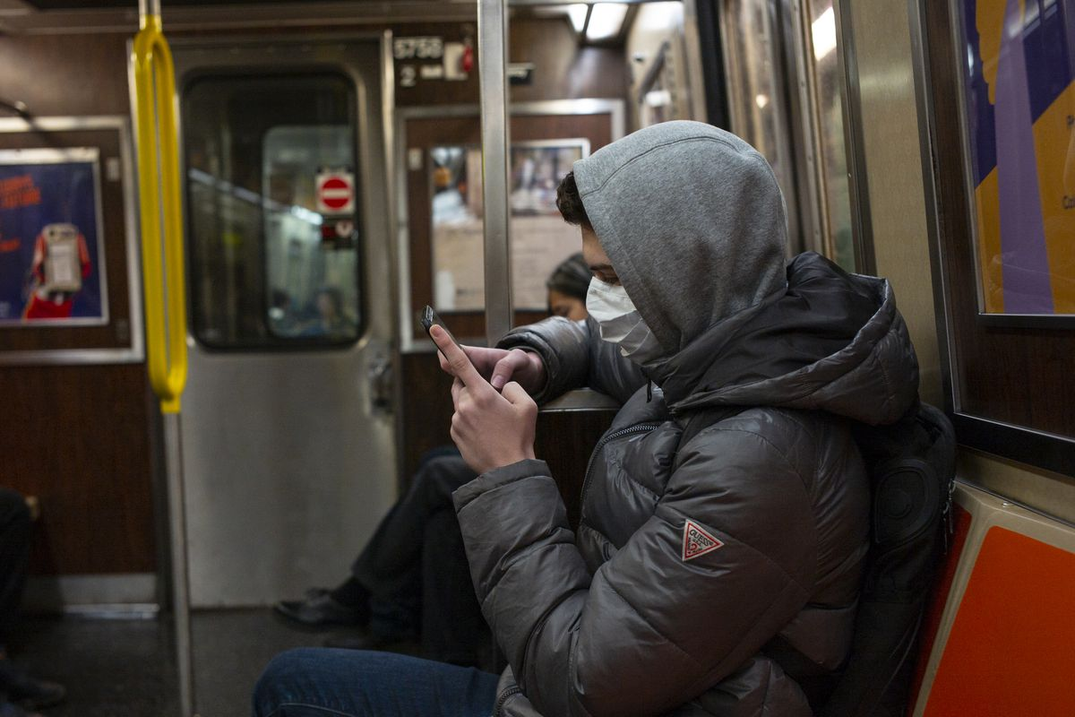 A man wearing a breathing mask and sitting on the New York City subway looks at his phone.