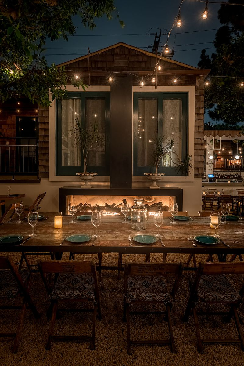 String lights outline large windows on an outdoor dinner patio.