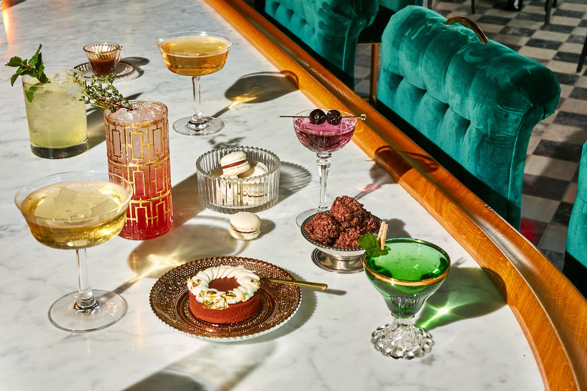 A spread of decadent desserts and cocktails in colors ranging from mint green to purple. There a circular red cake-like dessert sitting on a gold doily that's topped with meringue, a glass dish filled with white macarons, and brown balls of what looks like some sort of chocolate and oat mixture.