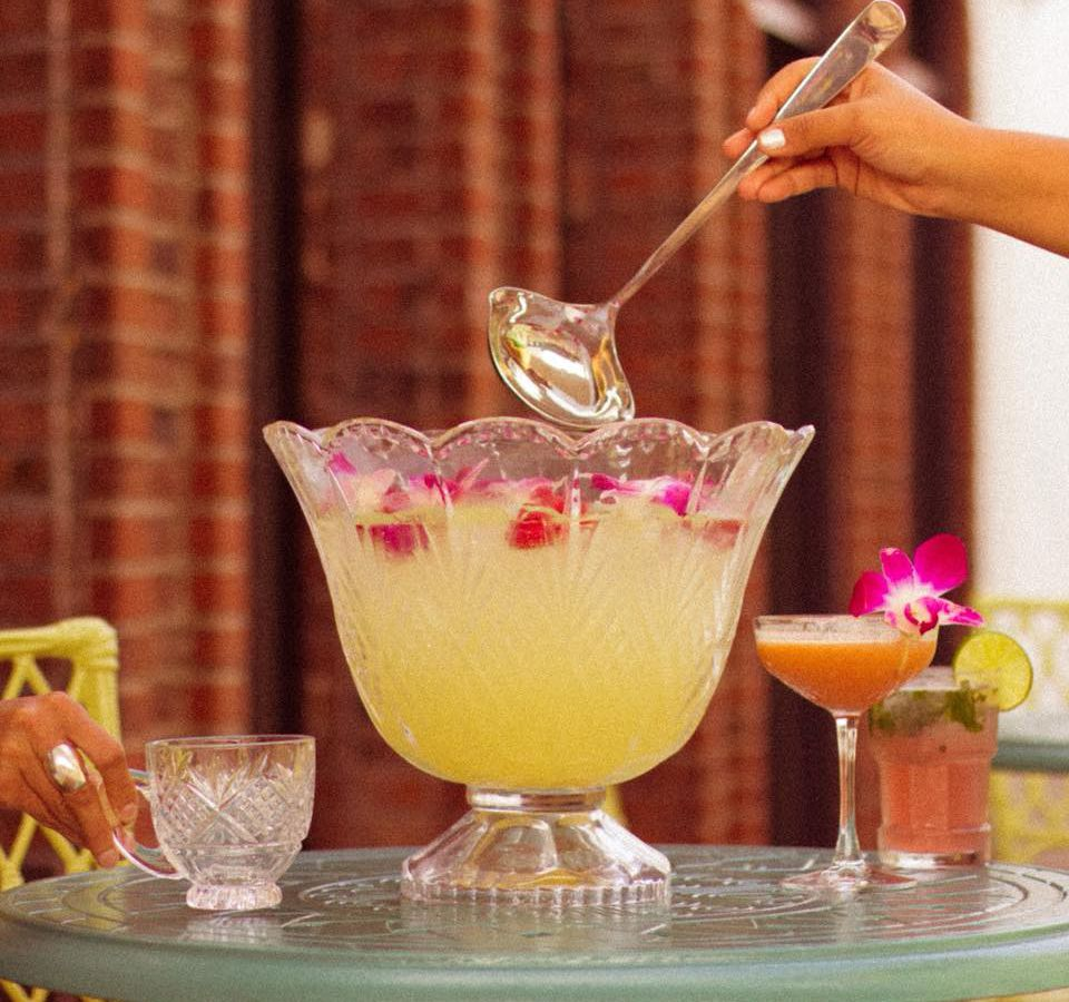 An elegant glass punch bowl is filled with a light yellow cocktail garnished with orchid petals. A few cocktail glasses surround the bowl, and a hand reaches in with a metal ladle.
