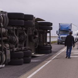 Bob Williams and Kenny Phillips clean the road after semitrailer was toppled by the wind on I-80 near Dugway on Monday, June 12, 2017.