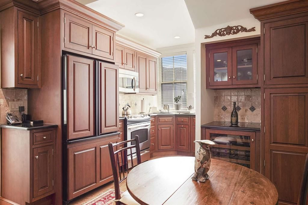 A kitchen with a table and chairs, the fridge looks like the cabinetry.
