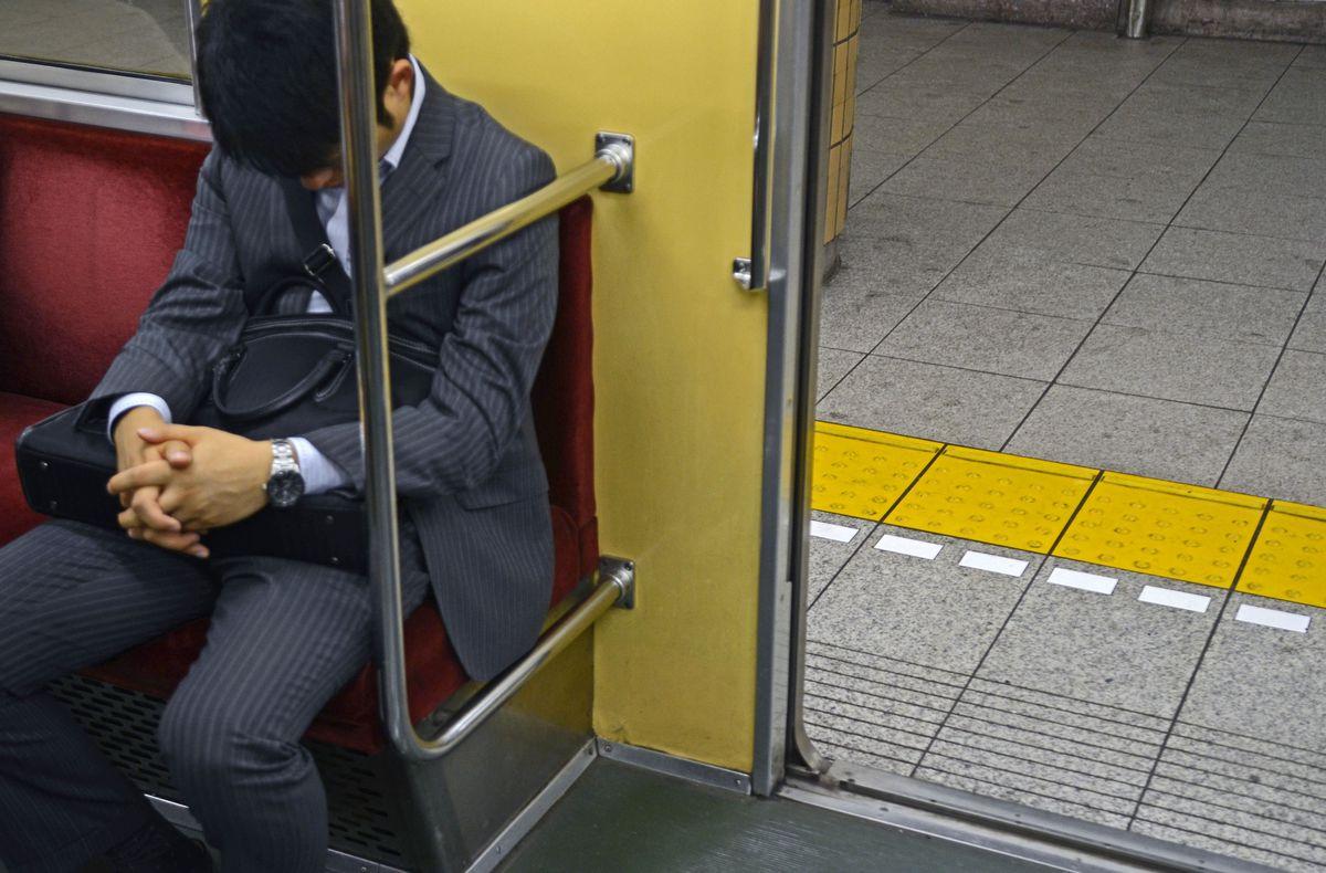Businessman sleeping in subway train, Tokyo.