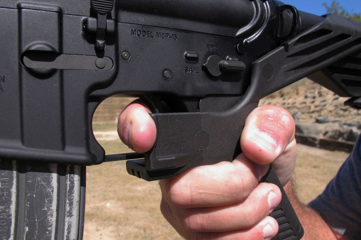 """FILE - In this Oct. 4, 2017 file photo, a shooting instructor demonstrates the grip on an AR-15 rifle fitted with a """"bump stock"""" at a gun club in North Carolina."""