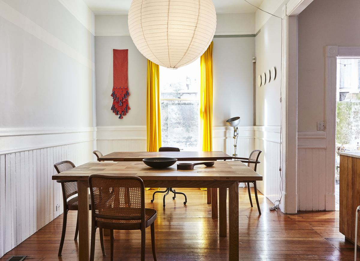 A dining area with a large wooden table, chairs, a light fixture hanging over the table, and a hardwood floor. The window has bright yellow curtains.