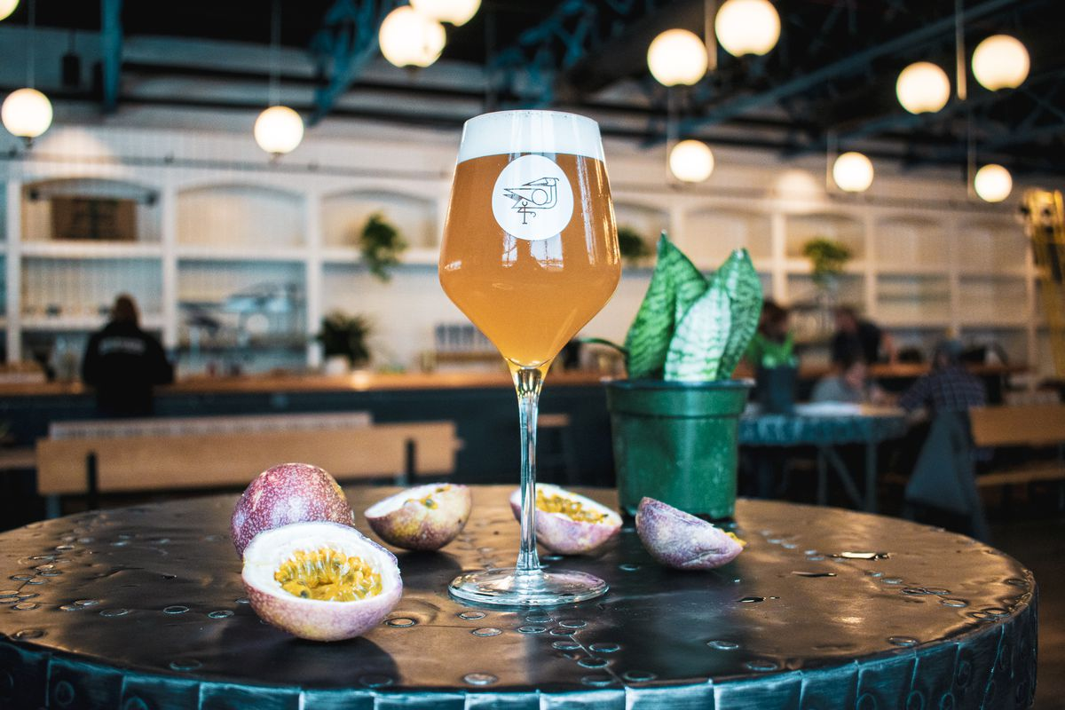 A tulip glass filled with beer and surrounded by sliced passionfruit.