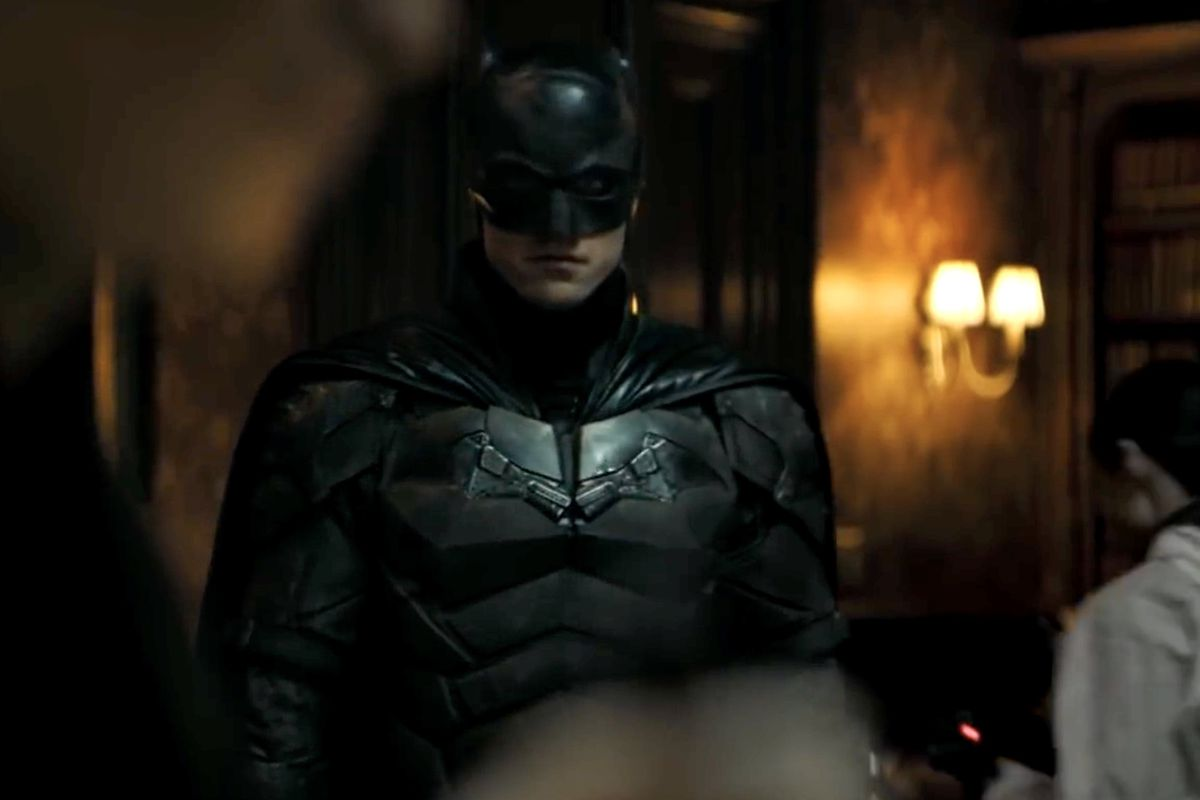 Robert Pattinson as The Batman standing in a mansion surveying a murder in the DC Fandome 2020 trailer