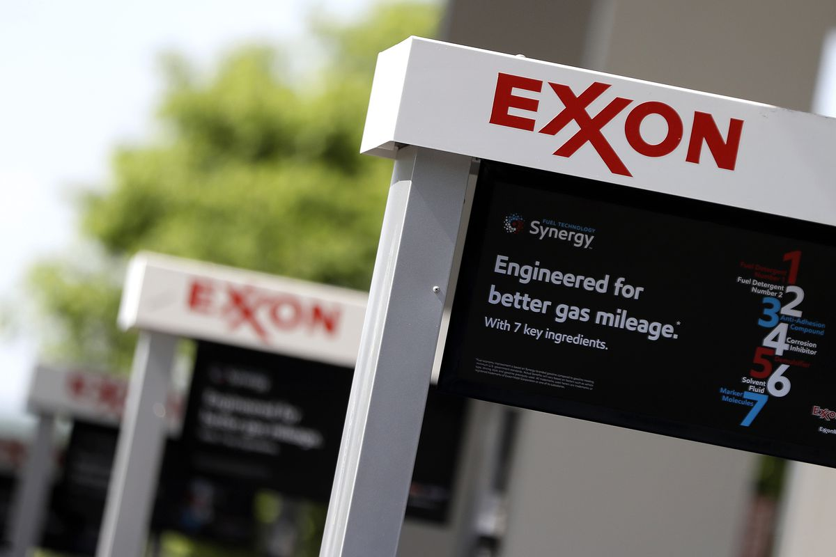 FILE- This April 25, 2017, file photo, shows Exxon service station signs in Nashville, Tenn. New York's attorney general is suing Exxon Mobil saying the company misled investors about the risks climate change posed to its business.