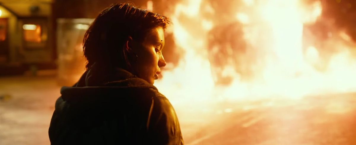 Rooney Mara as Lisbeth Salander stands in the foreground while a car burns in the background in The Girl With the Dragon Tattoo