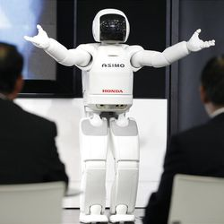 Visitors watch a Honda Asimo robot performing at a showroom at the headquarters of Honda Motor Co. in Tokyo Friday, April 27, 2012. Honda's January-March profit jumped 61 percent as the Japanese automaker sold more cars and motorcycles in a turnaround from a disaster-battered 2011. It forecast record global sales of 4.3 million vehicles for this fiscal year. (AP Photo/Koji Sasahara)