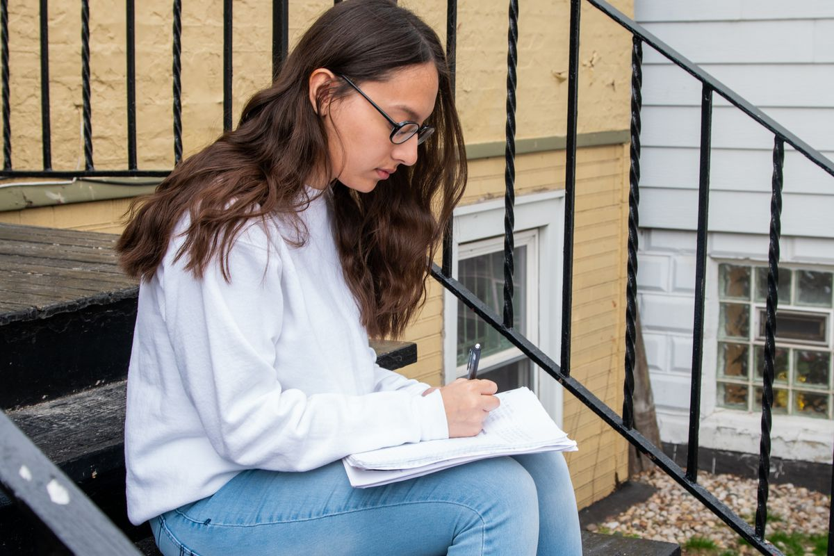 Marlenne Garcia does school work Friday on the steps of her McKinley Park home.