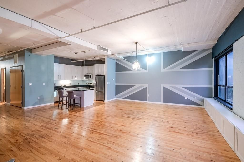 A cavernous empty living room with a kitchen to one side and shiny floors, and there's a painting of a Union Jack across one wall.