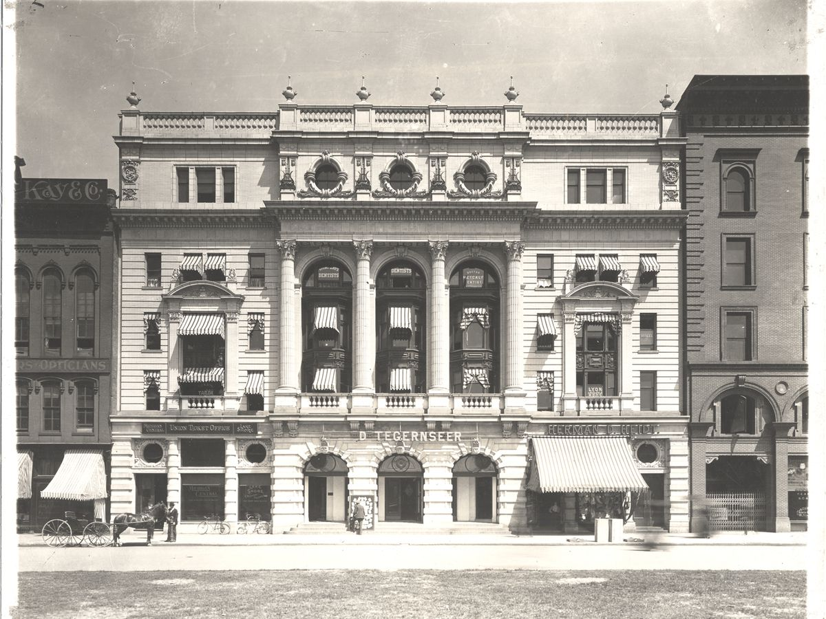 A vintage photograph of Detroit's Second Opera House. The facade is intricately designed with columns and white brick.