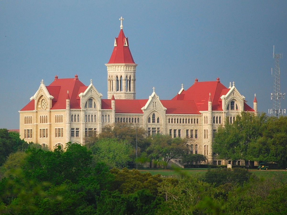 Large gothic-style complex on hilltop—stone with red roofs