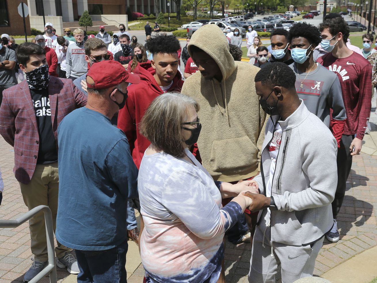 Alabama basketball players and coaches console Bryan and Pam Ratliff during a memorial for their son Luke Ratliff, on the steps of Coleman Coliseum on Saturday, April 3, 2021.