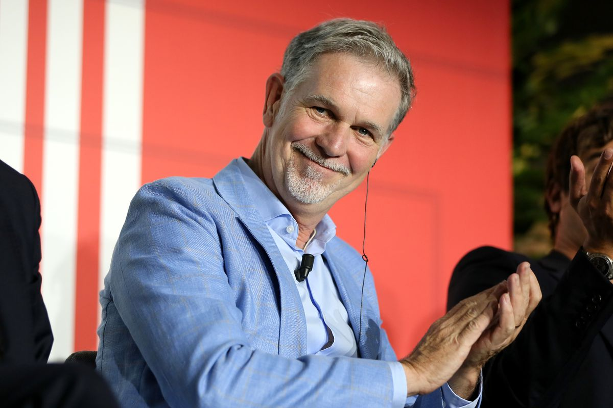 Netflix CEO Reed Hastings smiling and applauding from his seat onstage.