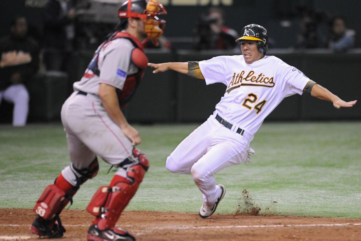 Oakland Athletics Kurt Suzuki (R) slides