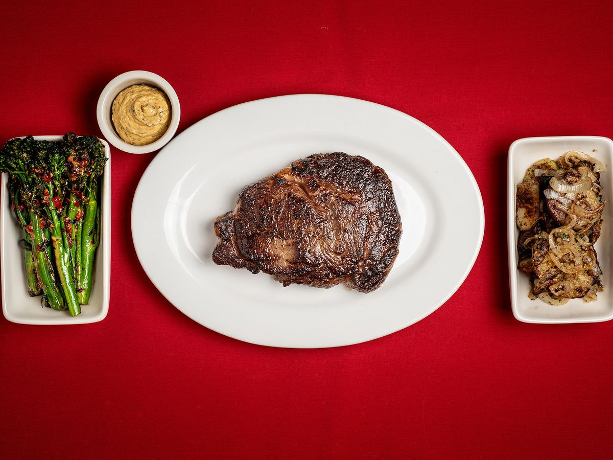 A seared steak with asparagus and sauce on the side.
