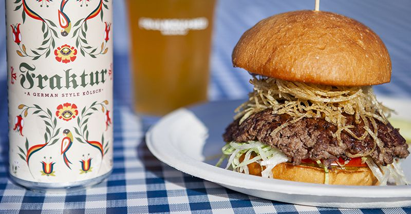 A white beer can decorated with green, red, blue, and yellow flowers, sits adjacent to a burger, topped with lettuce, tomato, and thinly sliced onion rings. The table on which the beer and burger sit is covered with a blue and white checked tablecloth.