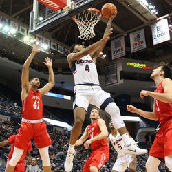 UConn's Jalen Adams (4) gets some air as he goes in for a reverse layup.