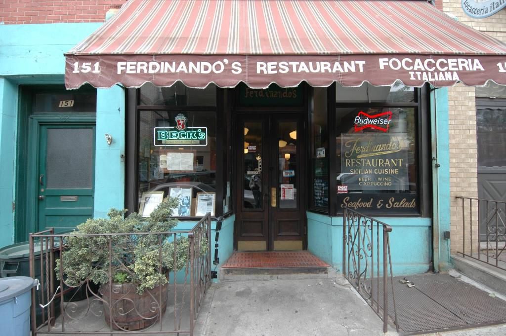 """The front of a small restaurant, whose red and blue striped awning reads """"151 Fernando's Restaurant Focacceria"""""""