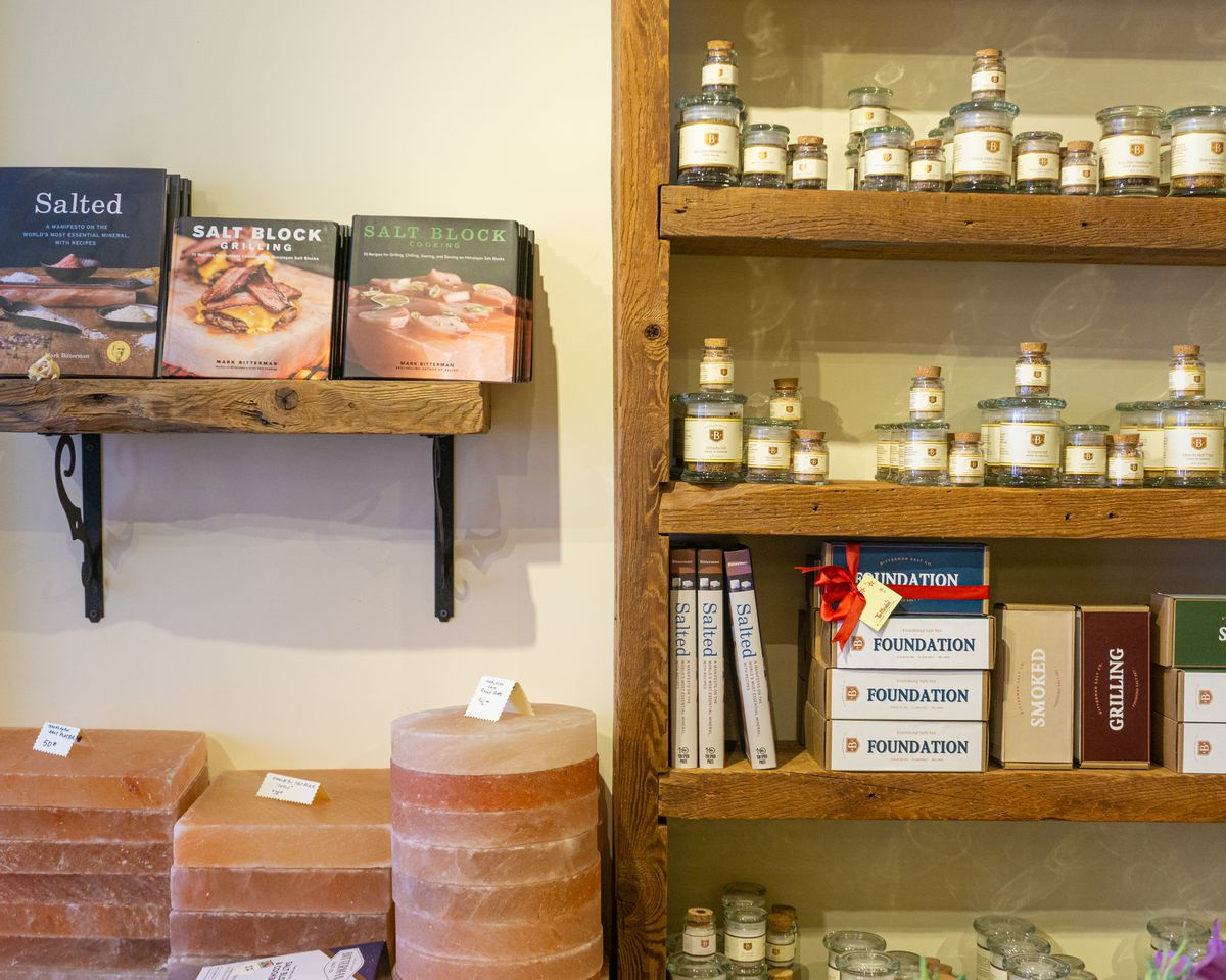 A shelf lined with bottles of salt, next to a pile of slabs of Himalayan pink salt, and a few books.
