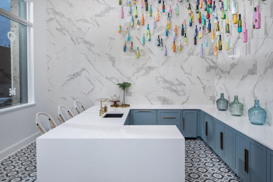 A kitchen with marble on the walls.