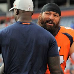 Broncos NT Domata Peko (right) embraces and chats with former Bronco player, current Broncos staff member DeMarcus Ware.