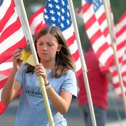 Neighbor Cora McIllece puts up flags around the house belonging to the father of U.S. Marine Staff Sgt. Darin Taylor Hoover Jr. in Sandy on Friday, Aug. 27, 2021. Hoover Jr. was killed in the suicide bombing at the Kabul Airport in Afghanistan.