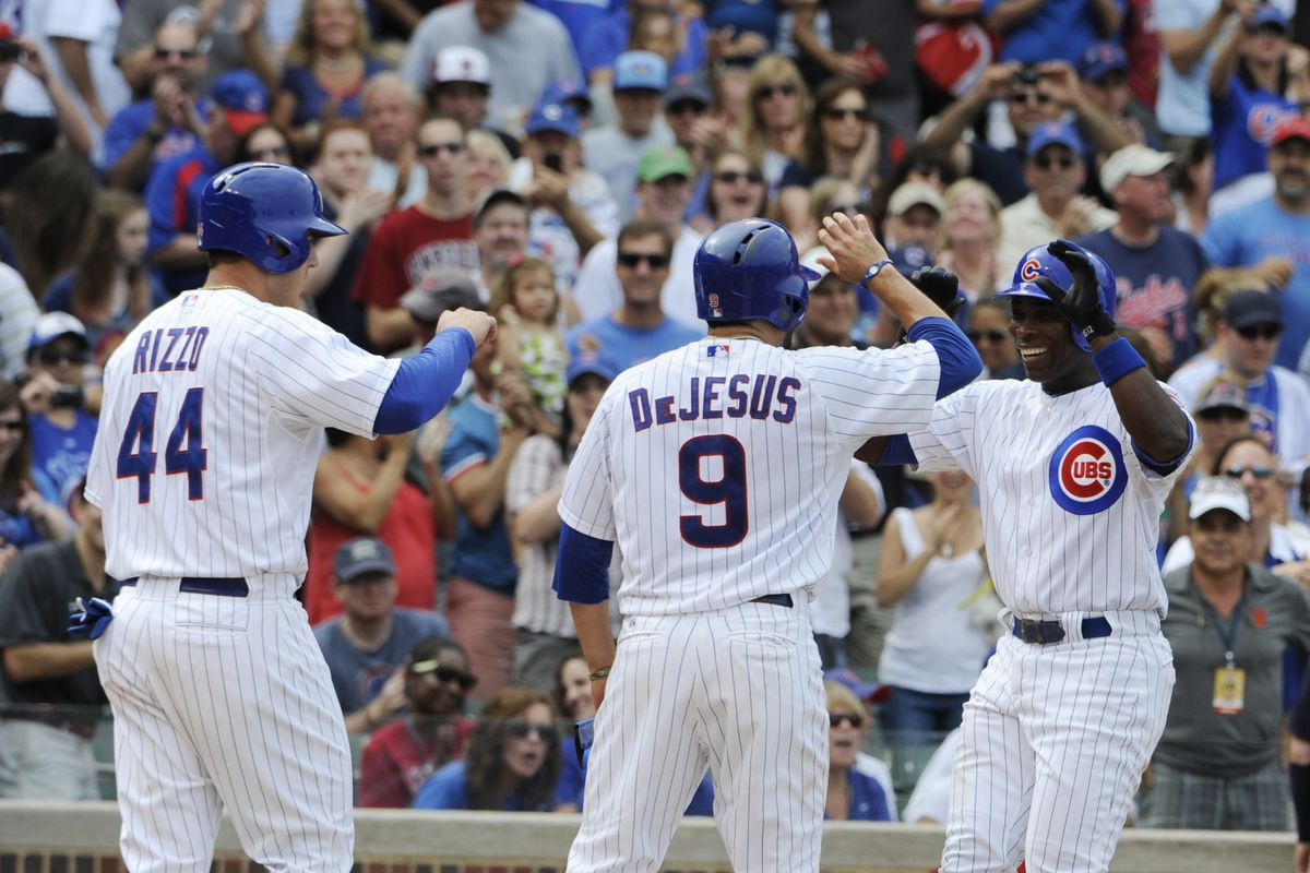 Alfonso Soriano of the Chicago Cubs is greeted by Anthony Rizzo and David DeJesus after hitting a three-run homer against the San Francisco Giants at Wrigley Field in Chicago, Illinois. (Photo by David Banks/Getty Images)