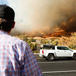 A man looks at the fire that broke out at the base of Mount Timpanogos in Orem on Saturday, Oct. 17, 2020.