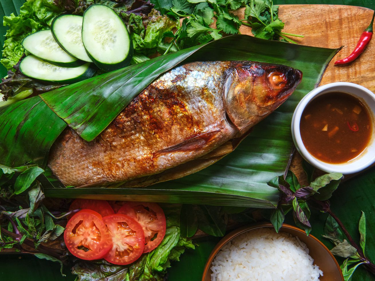 Cooked fish wrapped in banana leaves on a wooden board surrounded by sliced tomatoes, cucumbers, and next to a ramekin of sauce.