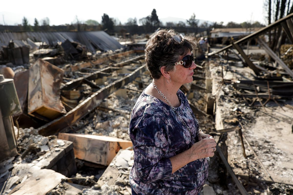 Anne Noble stands beside the remains of the home she shared with her husband, Bob, in Talent, Ore., while giving journalists a tour on Saturday, Sept. 19, 2020. Their home was one of more than 2,300 residences destroyed when the Almeda Fire swept through the towns of Talent and Phoenix in southern Oregon.