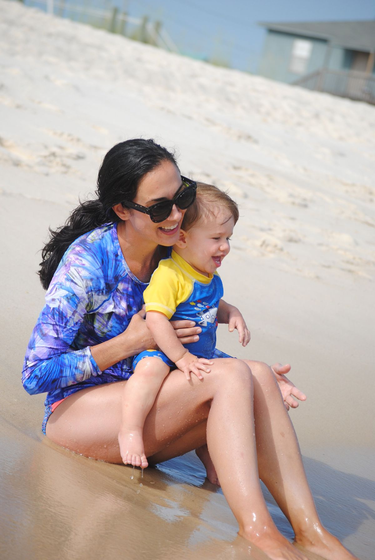 Nicole Hughes holding her son Levi on a beach outing.