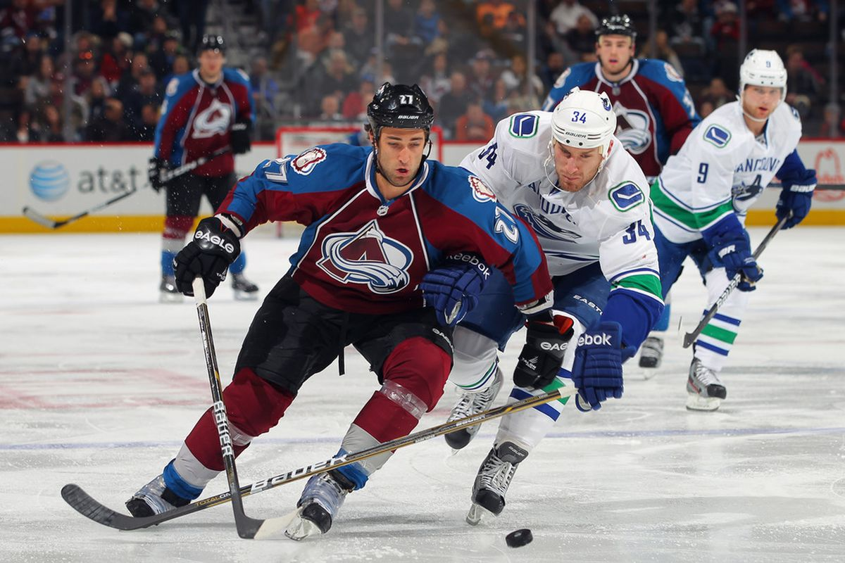 DENVER, CO - FEBRUARY 04:  Kyle Quincey #27 of the Colorado Avalanche controls the puck as Byron Bitz #34 of the Vancouver Canucks pursues at the Pepsi Center on February 4, 2012 in Denver, Colorado.  (Photo by Doug Pensinger/Getty Images)