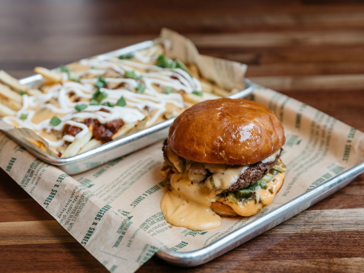 a burger with cheese melting onto the tray and fries with a white sauce and chives