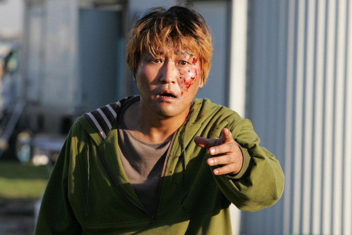 A man with blood spattered on his face points forward.