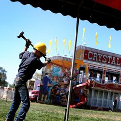 Trenidy Lewis hammers a stake while setting up a tent in preparation for the Utah State Fair at the Utah State Fairpark in Salt Lake City on Wednesday, Sept. 4, 2013. The fair runs Sept. 5-15.