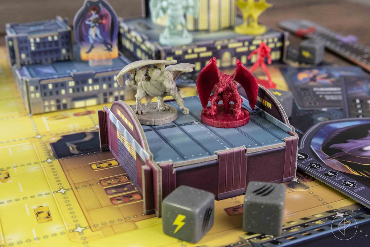 Two Gargoyles miniatures on top of a warehouse, about one inch off the game board.
