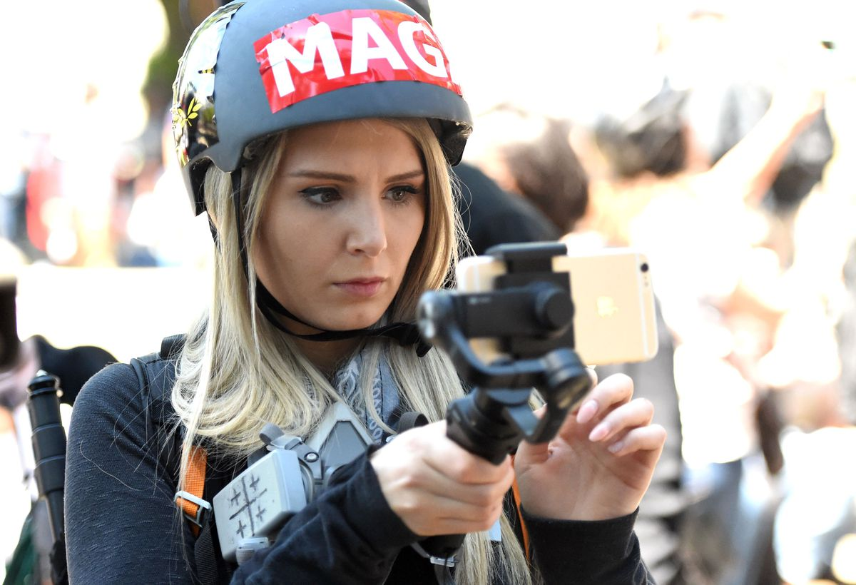 "A woman in a helmet bearing a ""MAGA"" sticker and carrying a cellphone in a hand-held camera rig."
