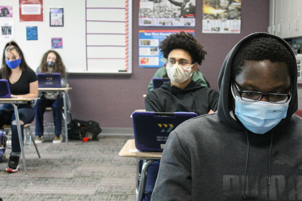 Four masked students sit at desks and look into laptops at Ben Davis High School in Indianapolis, Ind. on Friday, April 9, 2021.