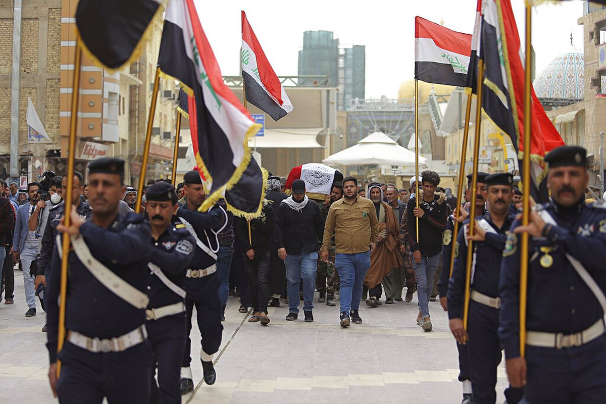 Mourners and militia fighters carry the flag-draped coffins