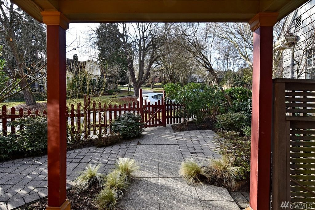 The view from the porch shows stone landscaping and a red picket fence